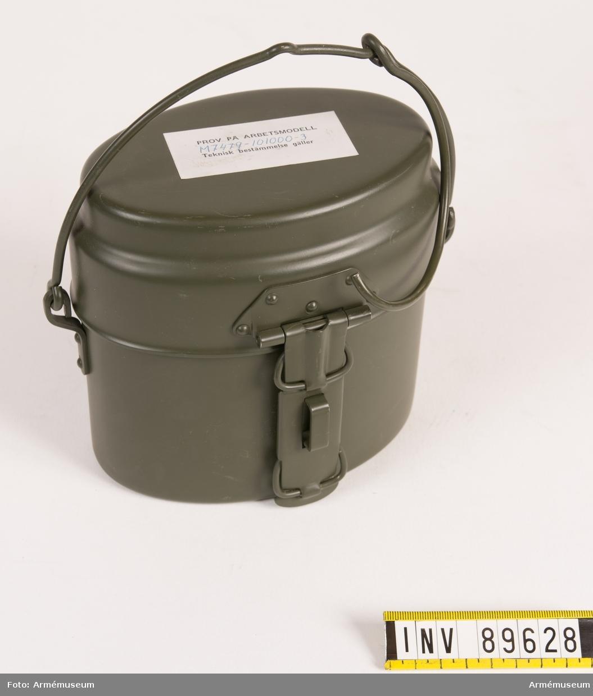 """Kokkärl grönmålad aluminium, invändigt omålad. På lockets baksida tre kronor-märkning och texten A-L E. Löstagbart lock med handtag. I locket kan födan stekas över öppen eld. För att klara värmen kan man sticka en förlängningsstav i de båda ringarna på skaftet. Kärlet har en grepe med krok, avsedd att hänga i över eld. Krokas även fast i ryggsäcken under transport. På locket finns en påklistrad lapp med text: """"Prov på arbetsmodell M 7479-101000-3 Teknisk bestämmelse gäller""""."""