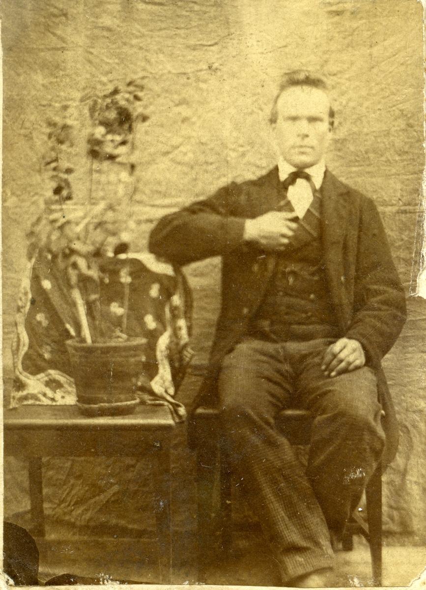 Ein mann sit på ein stol ved eit bord. På bordet står ei potteplante.