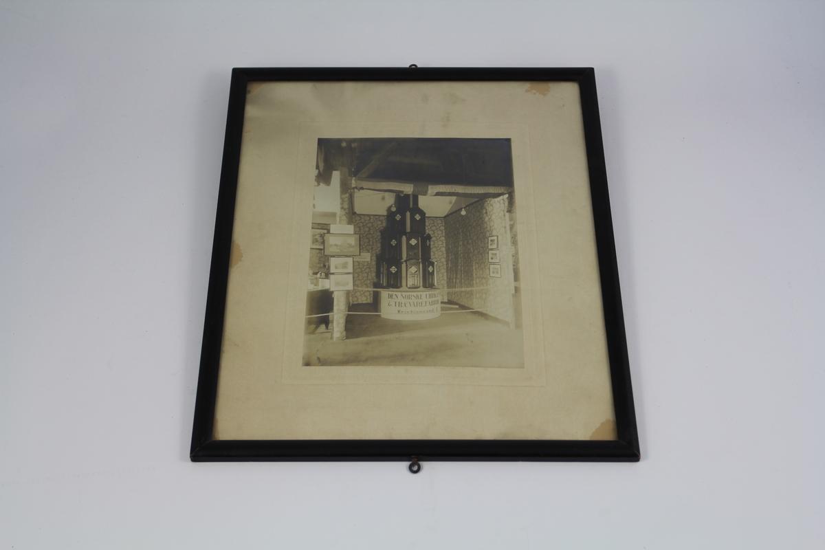 Fotografi av Den norske Uhrkasse & Trevarefabriks (innehaver snekkermester Niels Nielsen) utstilling i pakkhuset på Schmidts Kai i forbindelse med Den norske Uge i 1922.