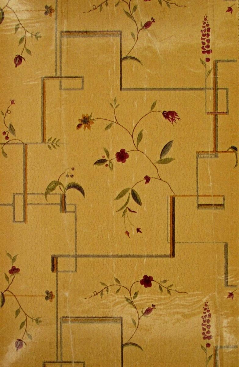 Stiliserade blommor och geometriska streck över ett litet stenimiterande mönster. Tryck i grönt, plommon, ljusbrunt och orange samt i två ljusblå nyanser på ofärgat papper.