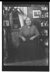 Eldre kvinne sitter i stol i stue. Blomstret tapet. Nips