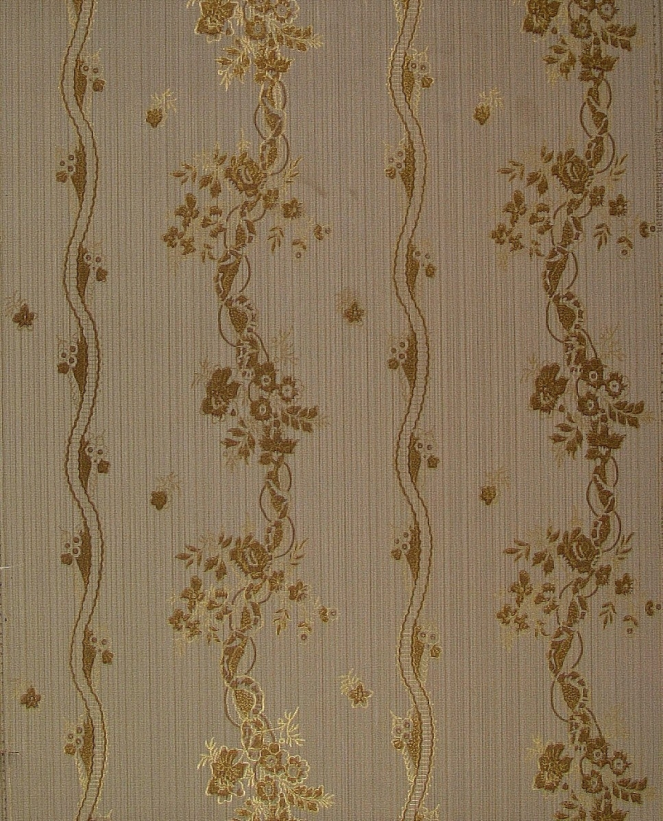 :: Ett vertikalt randmönster uppbyggt av slingrande rep omväxlande med blomrankor över en textilimiterande bakgrund. Tryck i guld och koppar över en bakgrund i ljusgrått och beige  dekorerad med någon guldrand.      Tillägg historik: Tapet från gårdsmagasinet på Bråborgs kungsgård - Norrköping.