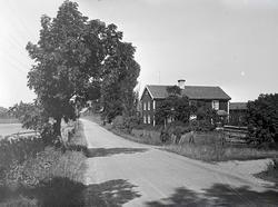 Mangårdsbyggnad och vy med bygata.