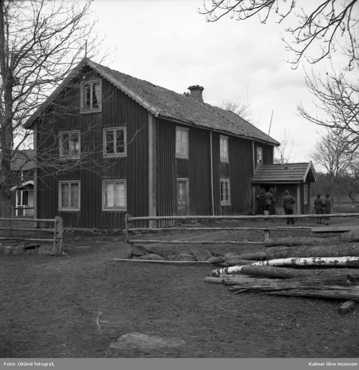 Bild på en manbyggnad, staket och timmer.
