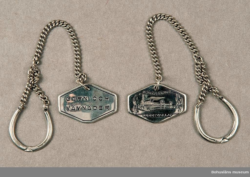 """Arbetade för Kampenhof 1927 till 1950-talets början. Kedja med en åttakantig bricka i ena änden och en ring i form av en hästsko i andra. På brickans ena sida står det stansat i svart: """"GARN OCH VÄVNADER"""". På andra sidan är står det: """"KAMPENHOF UDDEVALLA"""" samt är en bild på en byggnad. Givaren är son till brukaren/ägare."""