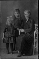 Studioportrett av kvinne og to barn.