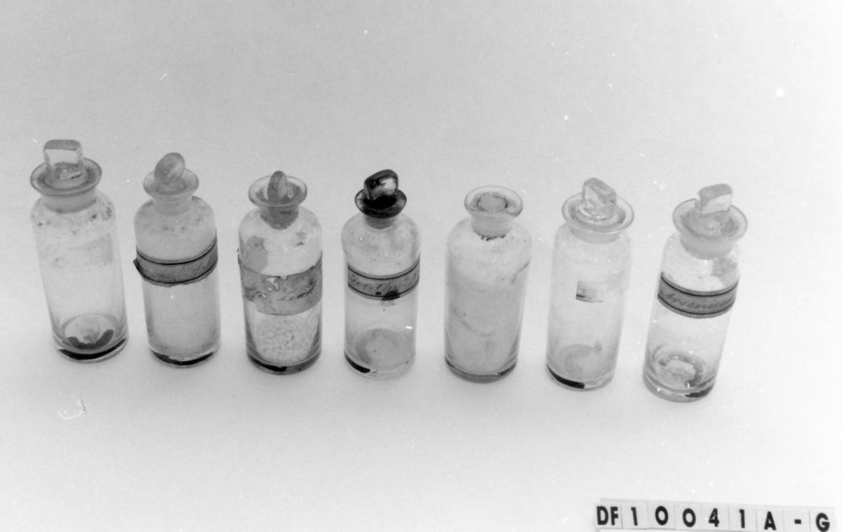 Tom flaske som antagelig har inneholdt et kjemikalie brukt til analyse av mineraler.  Blåst i form. Tilnærmet sylindrisk flaske. Slipt glasskork med rektangulært håndtak.