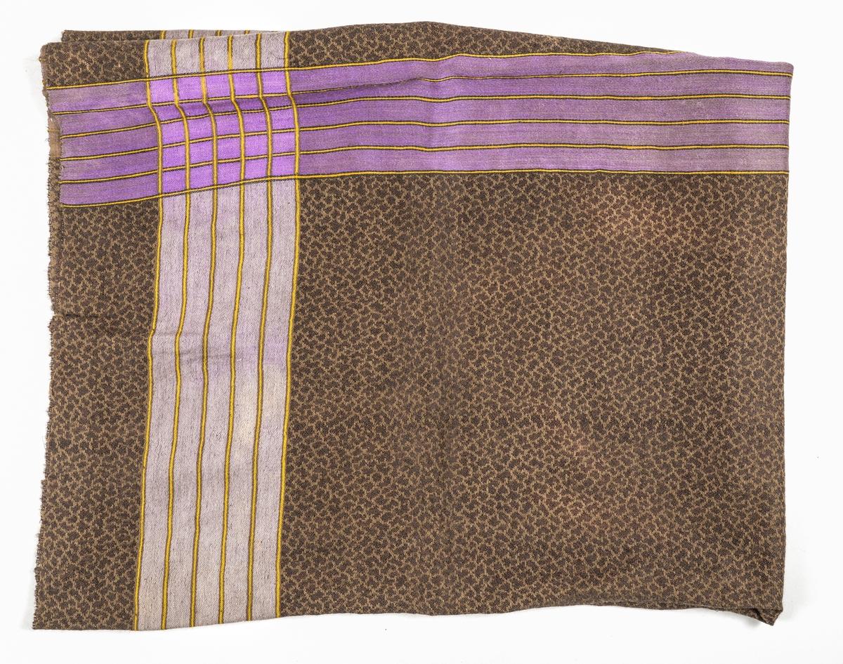 Tørkle i mønsterveing i brunt og svart med striper langs kantane i fiolett, gul og lys lilla. Falda (tråkla) på to sider, jarekant i dei to andre. Falden rakna i eine hjørnet.
