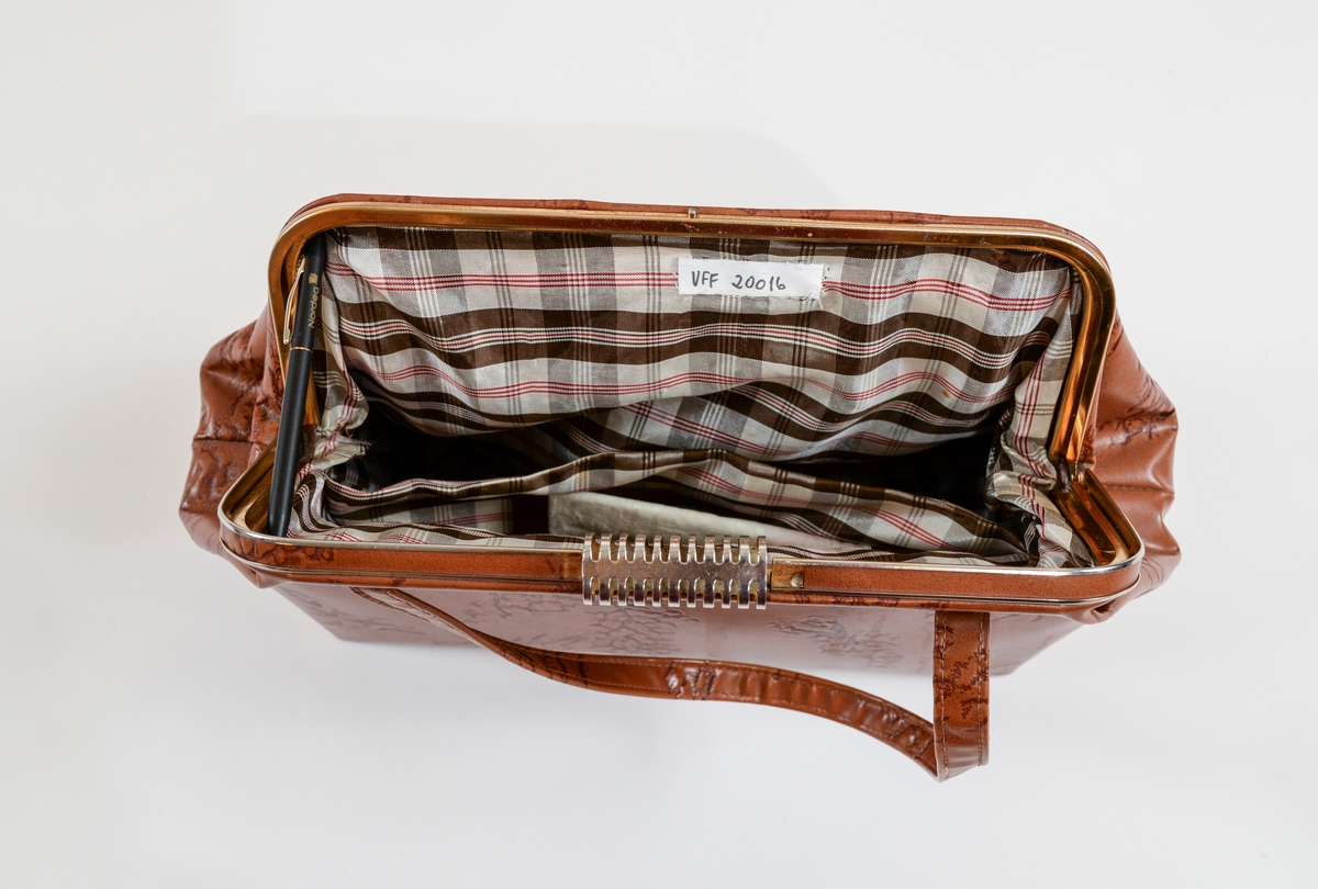 Lys brun dameveske i skinn. Fóra inni med rutut kunstsilke. Ei lomme inni veska, og ei utanpå. To hankar (48 cm lange).