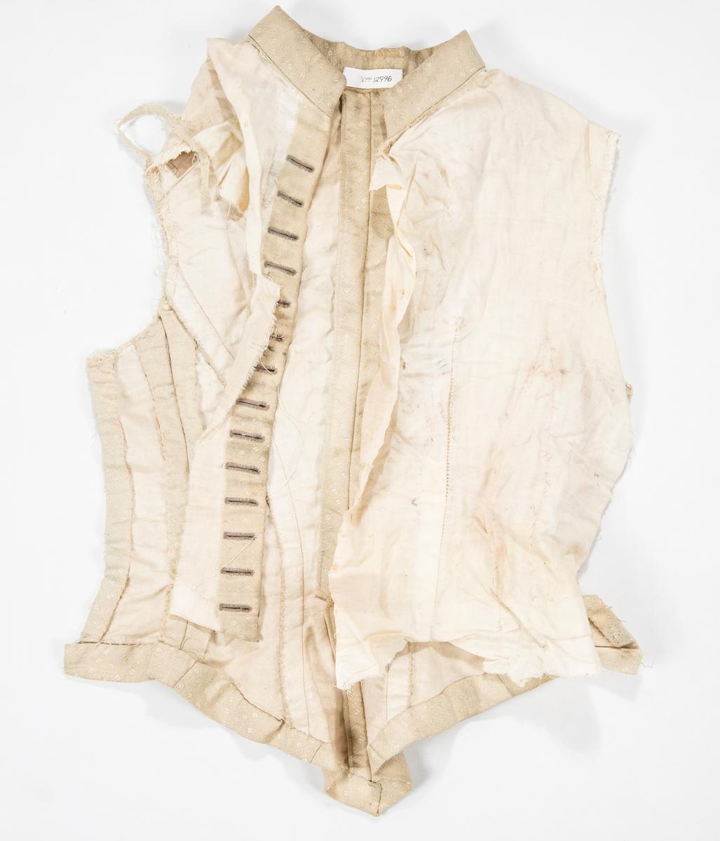 Del av kjoleliv i beige jacquardvove halvsilke, fòr i ubleika bomull.  Knapping midt framme, 14 knappehol, ingen knappar. Ståkrage. Saum midt bak og to svinga ryggsaumar på kvar side.