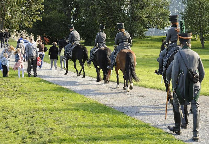 Fire ryttere i uniform som rir bortover en smal veg. Sett bakfra. (Foto/Photo)