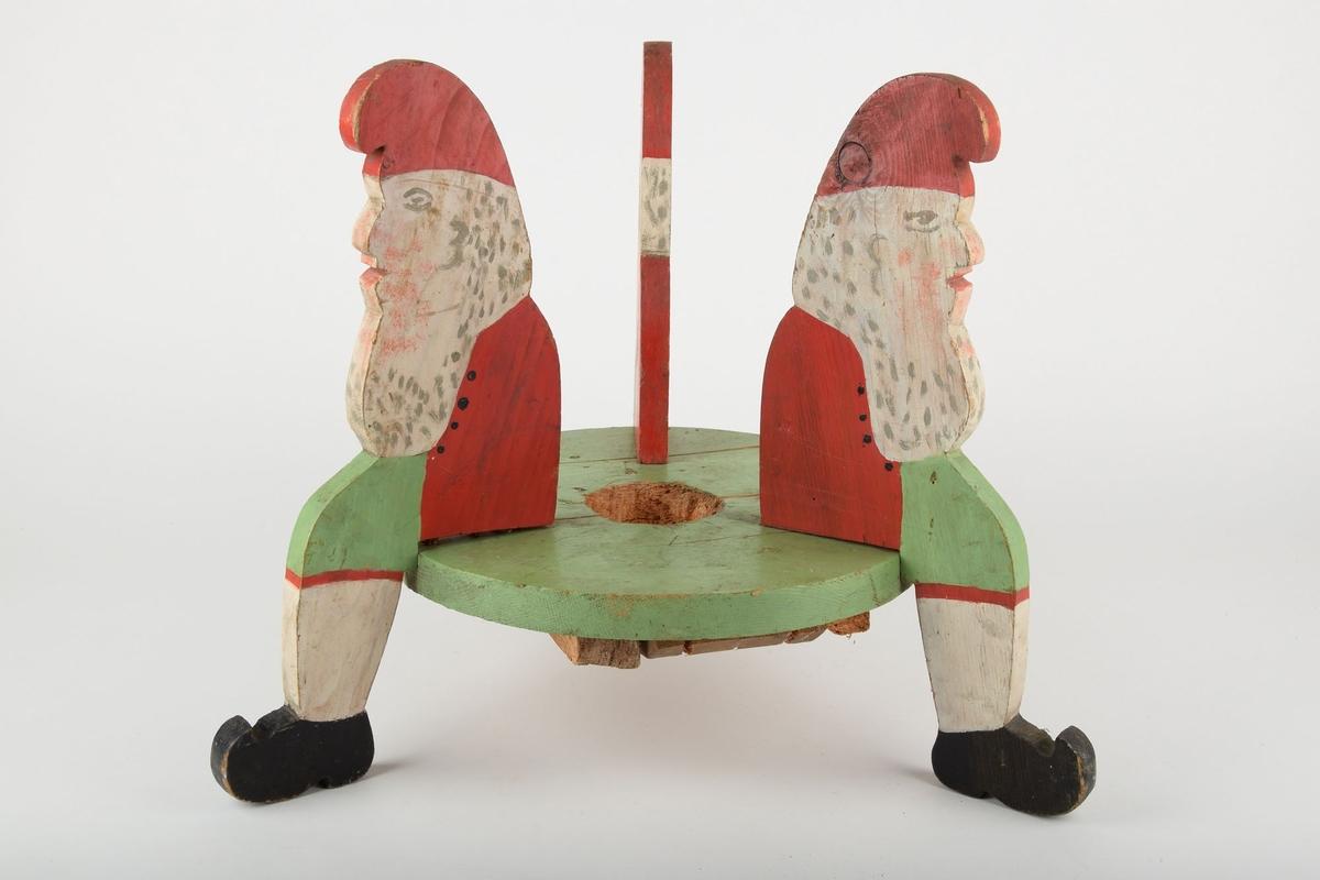 Juletrefot utskåret i tre, med 3 nisser som sitter rundt sirkelen hvor juletreet festes. Nissenes bein fungerer som gulvstøtter/føtter.  Den runde platen er malt grønn. Julenissene er dekorert med rødmalt lue, hvitt skjegg, rød jakke, grønne bukser med rød kant langs kneet, hvite knestrømper og svarte sko.