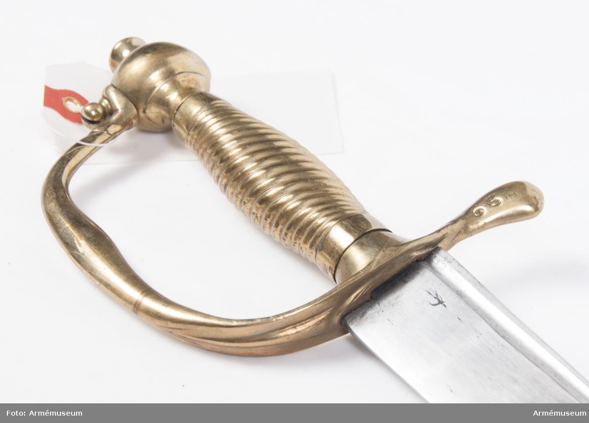 """Vapnet är en ändrad huggare m/1748, där yttre och inre parerplåten bortslipats. Eneggad krökt klinga och fäste av mässing. Märkt """"29"""" på parerstången. Klingans bredd vid fästet: 35 mm."""