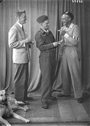 Gruppebilde. Tre menn, en i uniform og en hund. Bestillt av