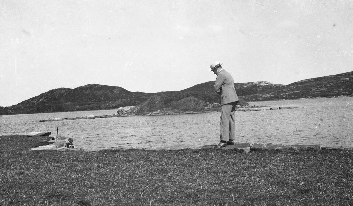 Gruppebilde. Sommer. En mann står med follete armer ved sjøkanten og ser ned i sjøen. Berg og holmer i bakgrunnen. Hverdagsfoto.