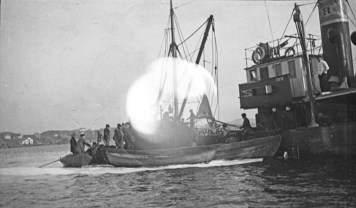 Fiske. Flere småbåter leverer fisk til et større fiskefartøy. Mange personer i arbeid. Bebyggelse i bakgrunnen. Hverdagsfoto.
