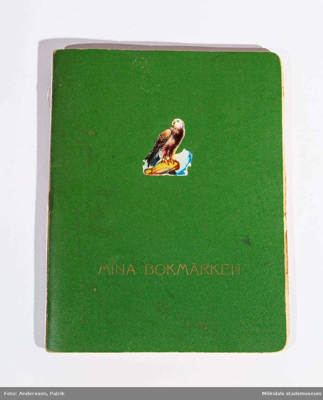 Bokmärkesbok med inklistrade, tidstypiska bokmärken. På framsidan står tryckt: MINA BOKMÄRKEN. Ett bokmärke, föreställande en örn, är klistrat ca 10 cm ovanför texten. Boken ägdes/användes av givarens mor Ninnie Johansson.