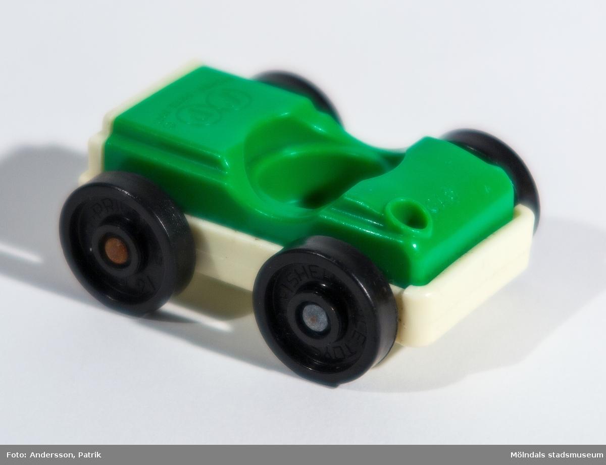 """Leksaksbil utan tak, grön/vit, med fyra svarta hjul tillhörande Fisher-Pricegarage från 1970-talet. Rund försänkning i mitten med plats för figur (chaufför). På bakluckan, till vänster,  finns ett hål att """"tanka"""" bensin i. Inköpt 2001 på Second Hand av givaren, vars barn har lekt med det."""