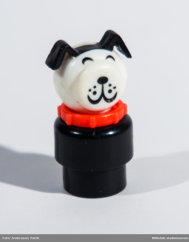 """Rund hundfigur av plast tillhörande Fisher-Pricegarage från 1970-talet. """"Kroppen"""" består av två delar varav den nedersta är smalare för att passa ihop med tillhörande leksaksbil. Ihålig underifrån och längst in är """"huvudet"""" fastskruvat. Mellan kropp och huvud sitter ett hundhalsband. """"Huvudet"""" består av en något tillplattad plastkula med markerade hundöron samt målade ögon, morrhår, nos och mun. Inköpt 2001 på Second Hand av givaren, vars barn har lekt med det."""