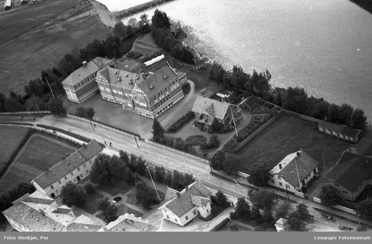 Flyfoto av Levanger, tatt av tenåringen Per Renbjør med sin fars Leica. Den gamle lærerskolen og rektorboligen mot sundet.