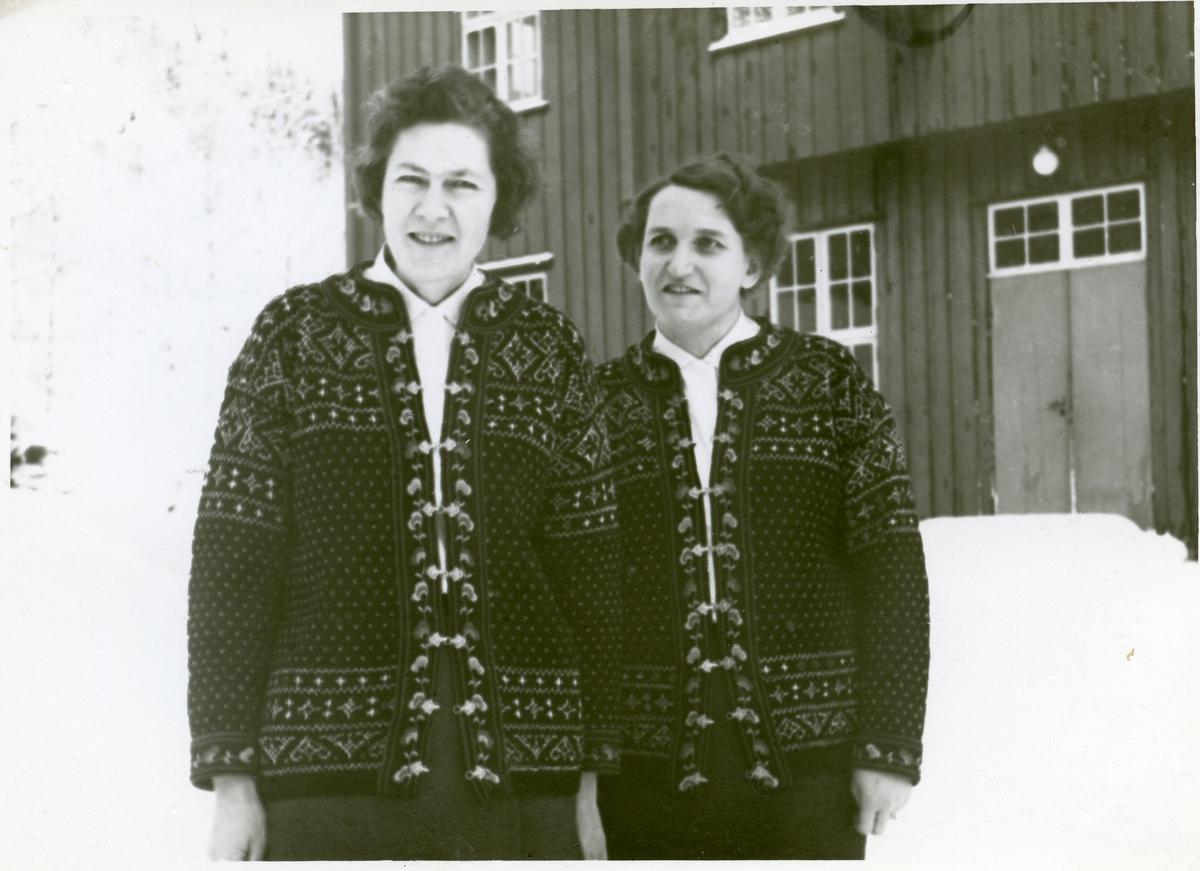 2 kvinner står utenfor et hus. Begge ha på seg hvite bluser og strikkekofter. Det er snø.