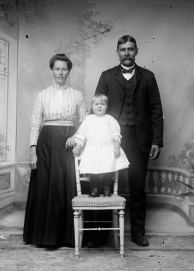 Ateljé. Par med en flicka stående på stol. Fotograf: Ellen