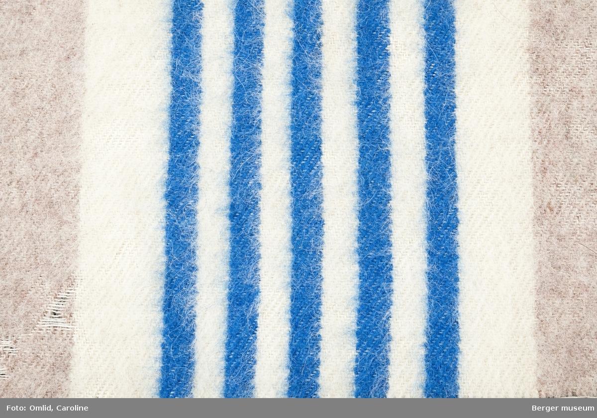 Teppeprøve med stripemønster. Brede striper i annenhver beige og off-white i teppet, smalere og tettere striper i kobaltblått og grålilla som tverrgående bord. Behandling: Oppfukting med vann i sprayform. Vask i varmt vann tilsatt 1 tsk Berol 784. Innsåping med Marseille-såpe. Skylling i 3 hold varmt vann. Tørking på bord, med vifte, ca. 5 timer.