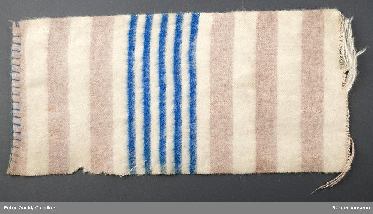 En prøve. Teppe i stripemønster; rosa og hvite striper.  Mønsterbord i smalere striper, fem blå og fire off-white.