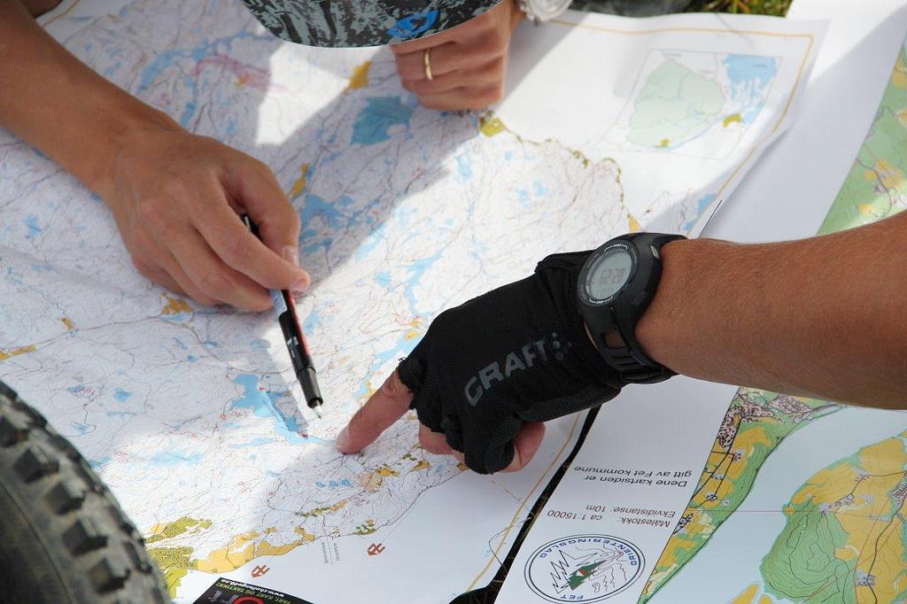 Foto av hender som peker på et kart.