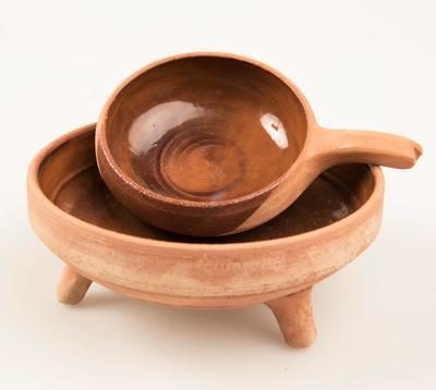 To keramikkskåler. Den største står på et hvitt underlag, oppi denne ligger det ei mindre skål med hank.
