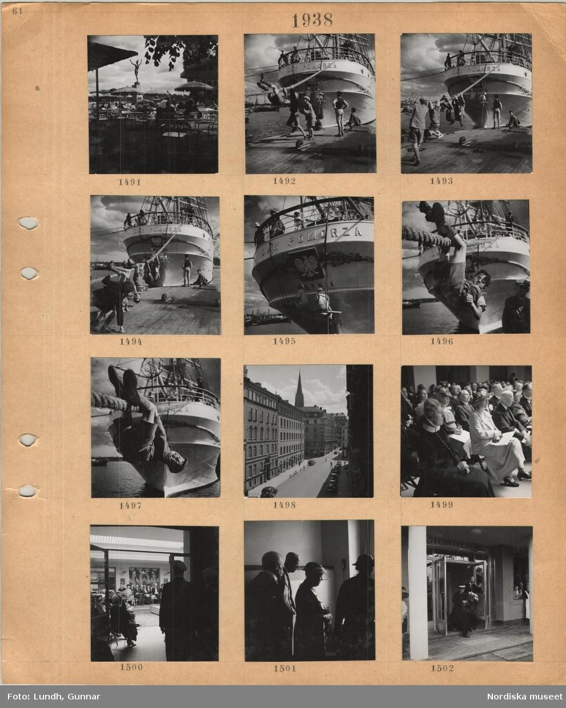 Motiv: Uteservering på Strömparterren i Stockholm, Carl Milles staty Orfeus, små runda bord, parasoller, gäster, aktern av segelfartyget Dar Pomorza från Gdynia vid kaj, lekande pojkar vid förtöjningsrepen, två män sitter på en bräda som hänger i rep och målar på aktern, gata med flervåningshus, parkerade bilar och cyklar, kyrktorn i bakgrunden, sittande publik inomhus, kvinna i dräkt och stor hatt, kvinna i sjuksköterskedräkt, män i kostym, kung Gustav V, fanborg, stående män med studentmössa, kung Gustav V och kvinna i hatt med blombukett i handen går ut ur Radimumhemmets entré.