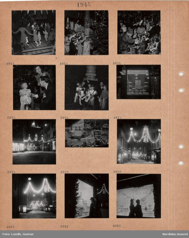 """Motiv: Barnkalas i offentlig miljö, barn och vuxna dansar runt julgran, män spelar fiol och dragspel, tomte delar ut presenter ur säck, liten flicka med present i handen, flickor sitter i knät på vuxna, skyltfönster till köttaffär med skylt """"Beställ julskinkan"""", gata med tända juldekorationer, skyltfönster med olika köttprodukter, en kvinna och en man tittar i upplyst skyltfönster med husgeråd."""