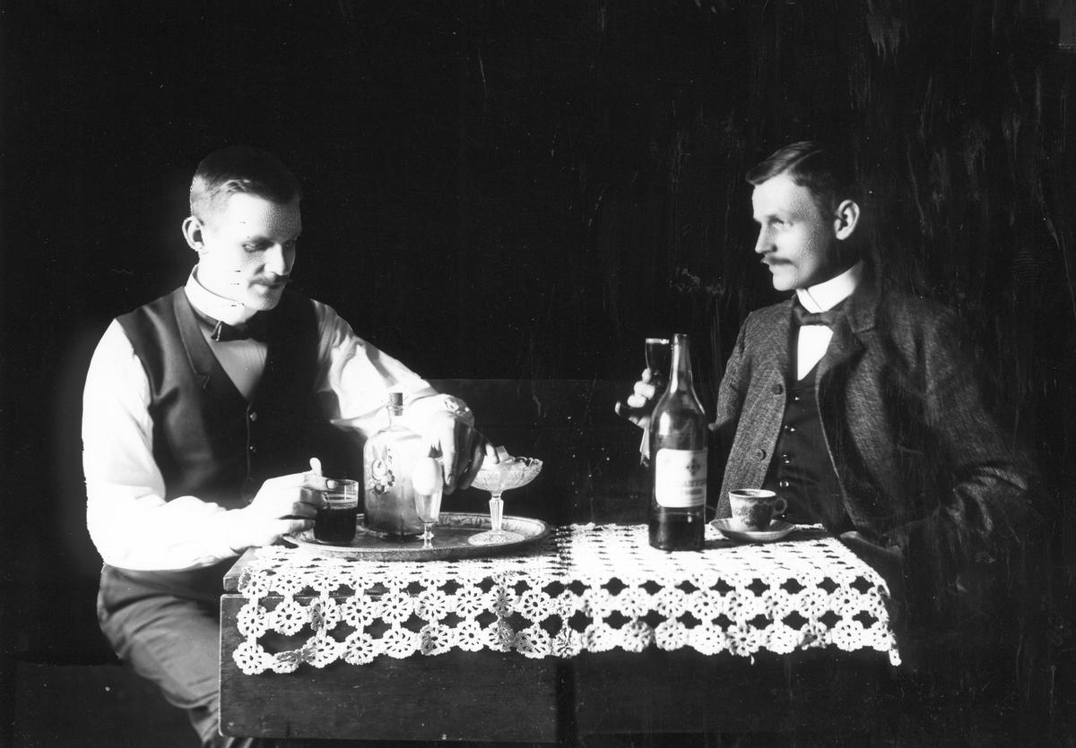 Två män som dricker snaps vid ett bord. Möjligen kan det vara ett trickfoto, där fotografen Karl Johan Östergren dubbelexponerat samma person.