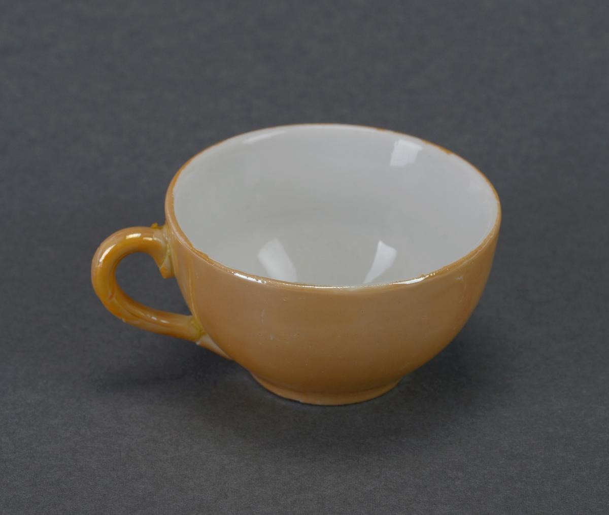 Et teservise for barn laget av keramikk. Gjenstandene er undernummerert 01-07. FTT.54459.01: En tekanne med løst lokk. Kannen er lav og bred. Tuten er svakt buet og hanken er firkantet i toppen mens den blir avrundet mot bunnen. Kannen er metallisk oransje på utsiden og hvit på innsiden. FTT.54459.02-03: To identiske tekopper som er metallisk oransje på utsiden og hvit på innsiden. Koppene er brede og har en buet hank i siden. Hanken på kopp FTT.54459.03 er limt. FTT.54459.04-05: To identiske tefat som er metallisk oransje på oversiden og hvit på undersiden. Det er en forsenkning i midten slik at koppene kan stå støtt. Kopp FTT.54459.04 er limt (to skår som er limt på igjen). FTT.54459.06: En mugge som er metallisk oransje på utsiden og hvit på innsiden. Den har en liten helletut og et lang hank på motsatt side. FTT.54459.07: en liten rund skål som er metallisk oransje inni og hvit på utsiden.