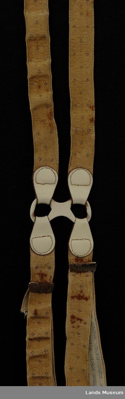 """Elastikken er lagt inn i et beige ripsbånd med små blå figurer. Midt i ryggen er et stykke kvitt lær, formet som en """"brille"""", 5 cm bred. I hvert hull er det tredd i et stykke lær, som dobbelt er sydd til en strikk, 2 cm bred, ca 25 cm lang. Nederst på strikken er det sydd på en hempe av lær med snittet knapphull. Disse delene festes i ryggen på buksa. Selene som kneppes på forbuksa er festet til """"brillen"""" som før beskrevet. Strikken er dobbel og har regulator av metall. Nederst er et stykke lær festet med bøyle i bukten av strikken. Lærstykket har bukt og patentknapp. I bukten ligger en rundvevd strikk med hempe i hver ende. Foran skal bukseselen festes til to knapper på hver side."""