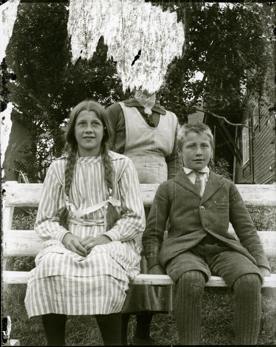 Jente og gutt sitter på en benk ute. Bak dem står en kvinne .