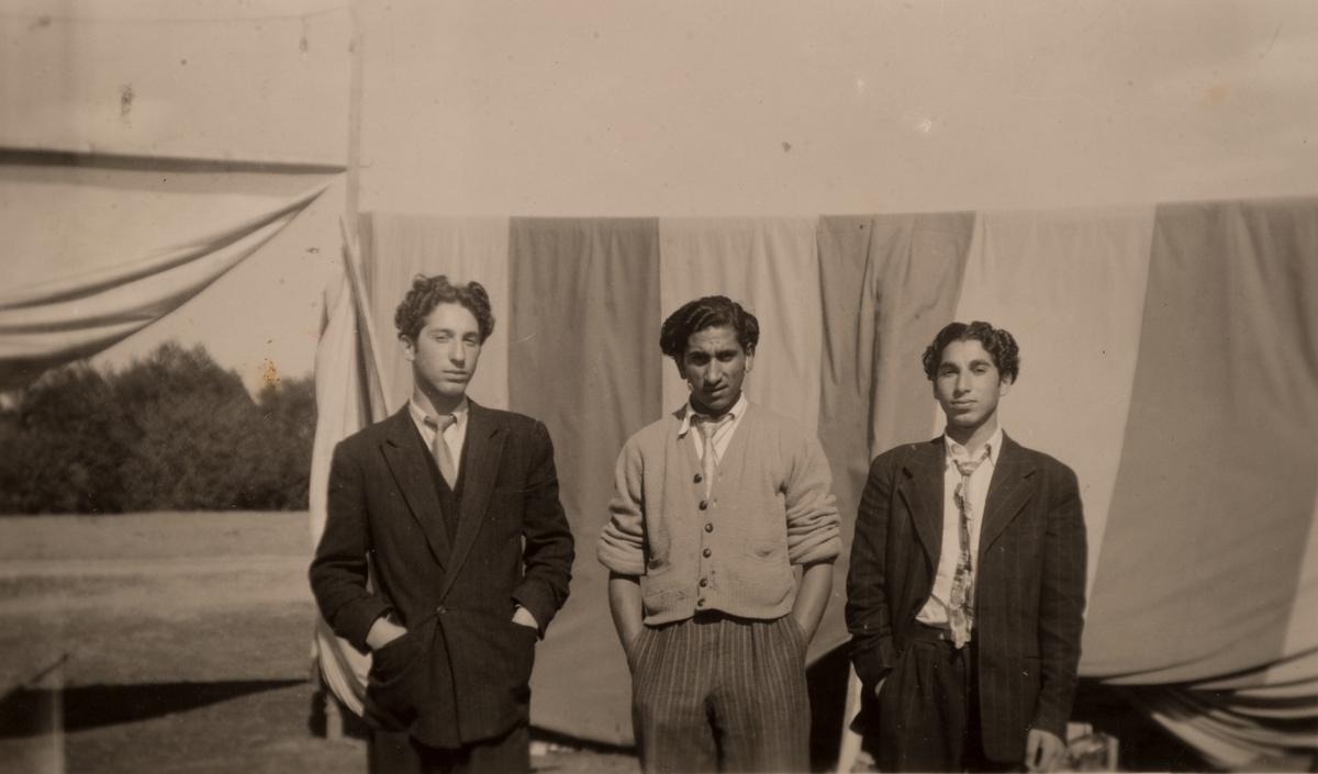 Tre unga romska män framför en upphängd tältduk. Det är känt att romer bodde i ett läger i Sandviken under sommaren 1947. Fotografiet är taget i juni detta år.