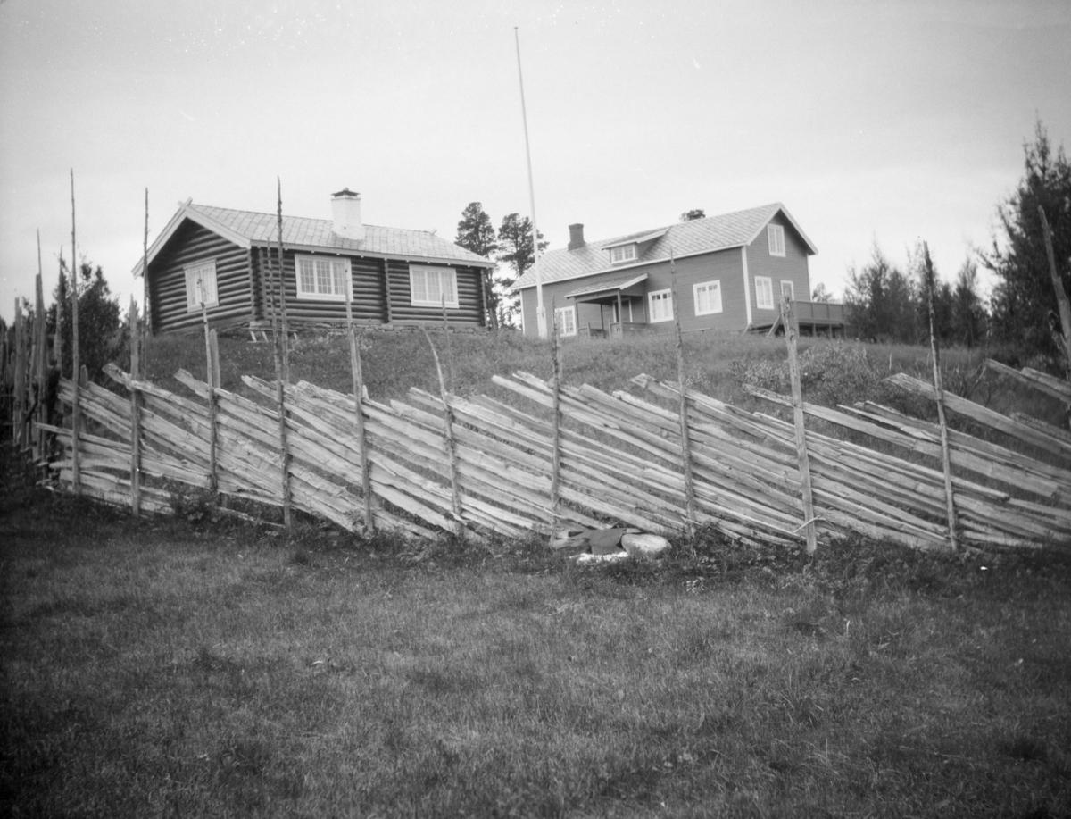 To hus, det ene i tømmer,  med  flaggstang i mellom.