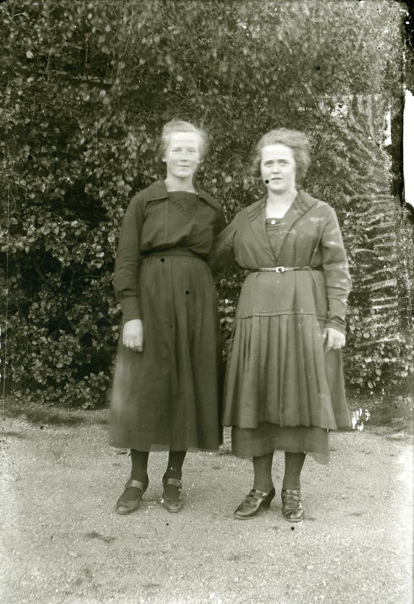To kvinner står ute foran ein hekk.