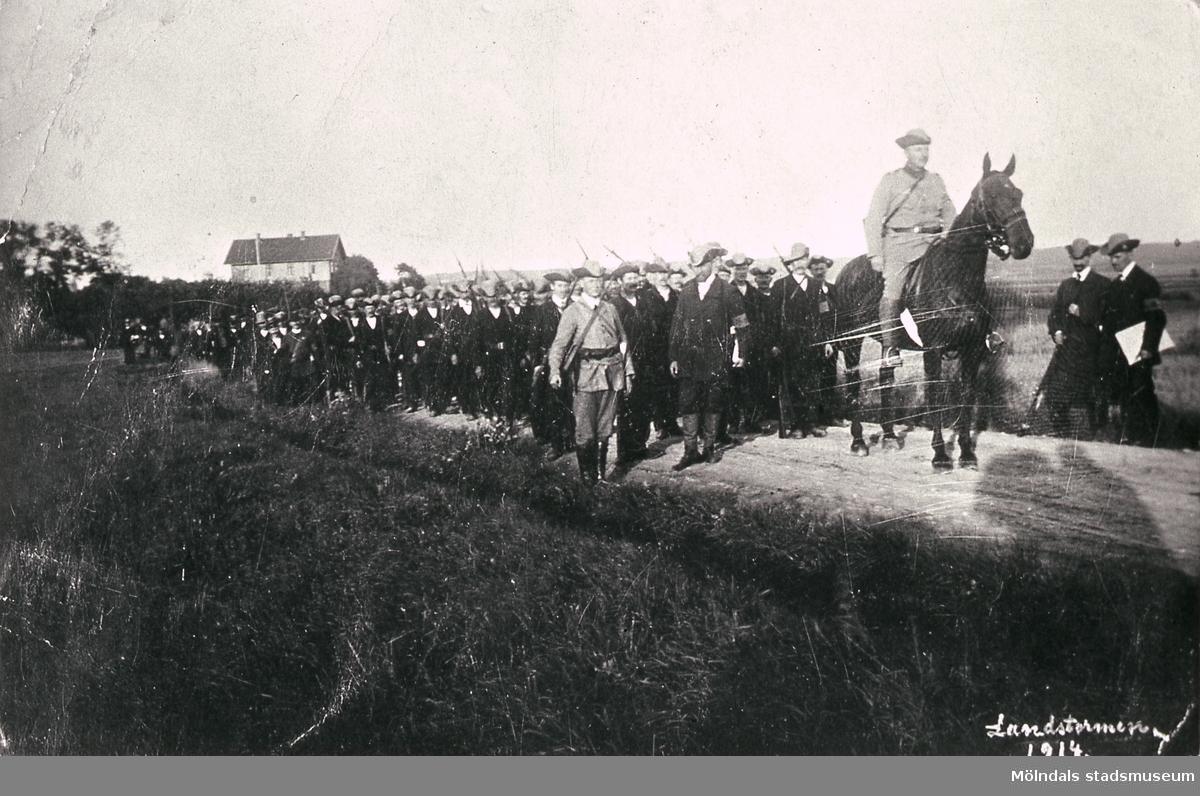 Landstormen på väg till Askim efter att ha utrustats på Trädgårdsskolan med armbindel, trekantig hatt och gevär, år 1914. I bakgrunden Fässbergs skola i Fässberg, Mölndal.