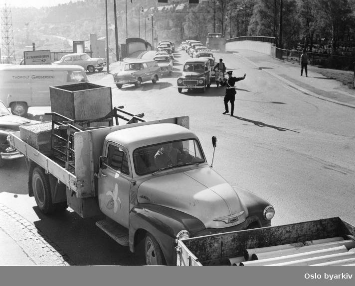 Politikonstabel som dirigerer biltrafikken i krysset Dyvekesvei, Bispegata, St. Hallvards gate. Dyvekes bru i bakgrunnen. Biltrafikk