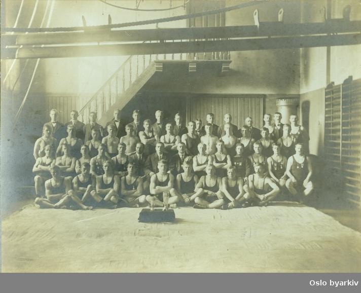 Gruppebilde av medlemer av Sportsklubben 1909. Signatur på bildet sier: Th. Thorkelsen Carl Johan Hj. Øvre Slotsgd. Hit flyttet fotografen i 1905. I fotografregisteret står det at etter 1919 spesialiserte han seg på gamle bilder og reproduksjoner. Bildet er altså trolig tatt en gang i perioden mellom 1905 og 1919.