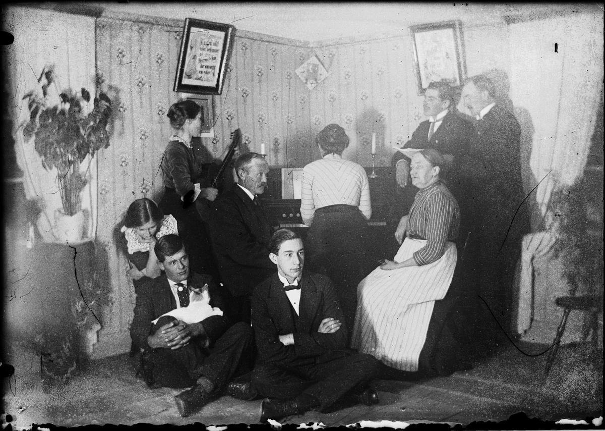Kvinnor och män samlade vid pianot, i hemmiljö, Östhammar, Uppland