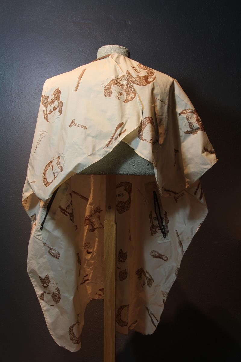 Form: avrundet, rektangulært stykke med halsringning, lukking bak. Stoffet har dekor som viser tegninger av barbersaker, børster og historiske menn med frisert hår, skjegg og/eller bart.