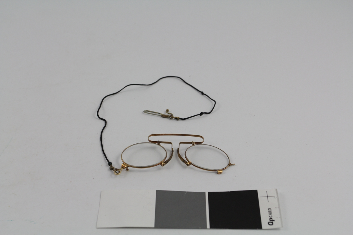 Form: ovale glass bundet sammen m/ innfatning og bøyle, snor m/ feste.