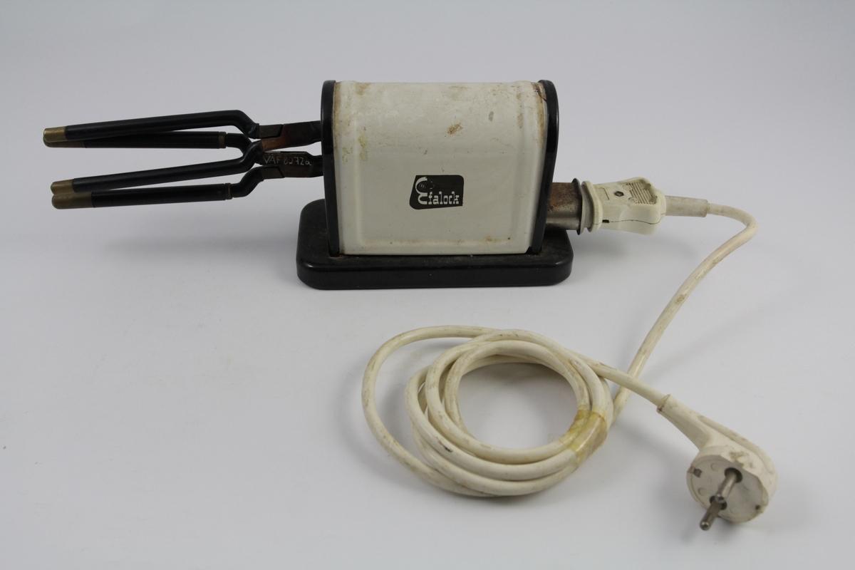 Eletrisk krølltang bestående av fire deler: a-b) krølltenger: 2 stk. sylindriske håndtak (a kan beveges).  Når håndtakene føres sammen, presses sylinder i andre enden ned i hul del.  c) elektrisk varmeapparat, uttak støpsel og ledning på den ene siden. Rektangulær sokkel. Påsatt rektangulær del med avrundet overside. Kortside: inntak for to krølltenger. Oval åpning.  d) Ledning med kontakter.