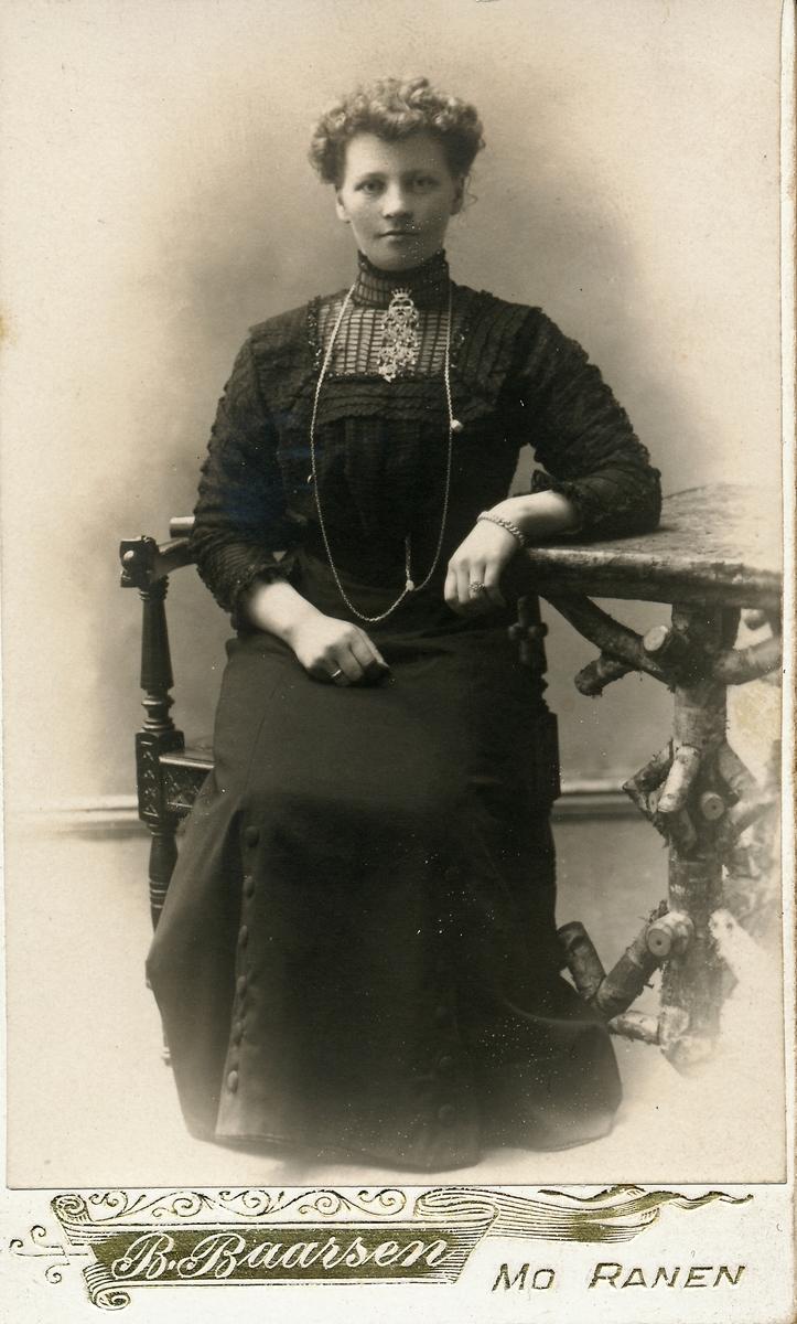 """Portrett av ung kvinne, sitter i stol ved """"rustikt"""" atelierbord. Hun har en stor sølje i halsen, krøllet hår."""