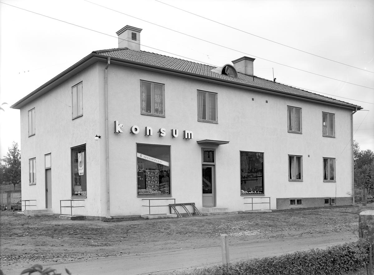 Vy mot den nyuppförda Konsumbutiken i Hjulsbro. Fastigheten uppfördes 1932 av byggmästare Gustav Salomonsson,  med fyra lägenheter på övervåningen och två på bottenplan. Det var tänkt att bli en privat butik i affärslokalerna, men när ingen nappade så sålde byggmästaren till tulltjänsteman Arvid Tilly som hyrde ut till Konsumtionsföreningen Linköping med omnejd. Butiken ombyggdes 1944 och blev större. Butiken upphörde 1976.