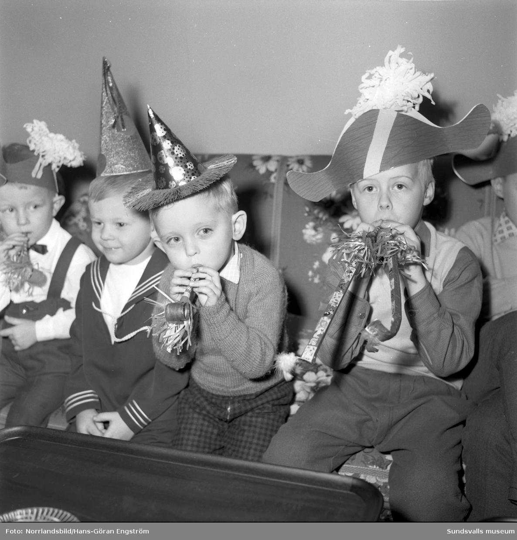Barnfest på Stadt. Finklädda barn med pappershattar och kalastutor.