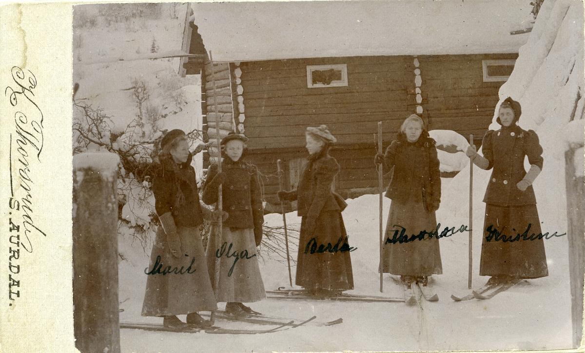 Fem unge kvinner står ute på gårdstunet med ski på beina.